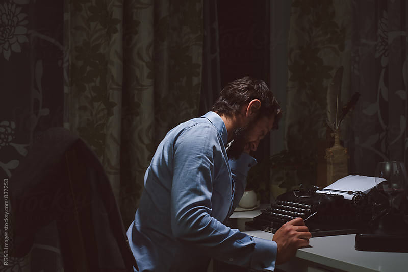 Writer with no inspiration sitting at  the typewriter  by RG&B Images for Stocksy United