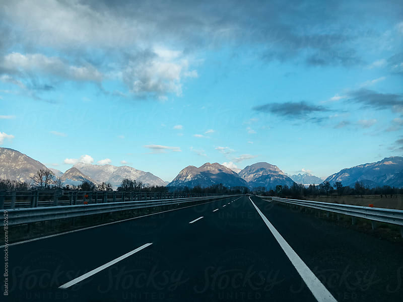 Empty highway with mountains on the horizon by Beatrix Boros for Stocksy United