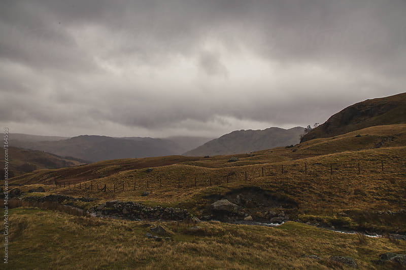 Dark clouds cover rolling hills by Maximilian Guy McNair MacEwan for Stocksy United