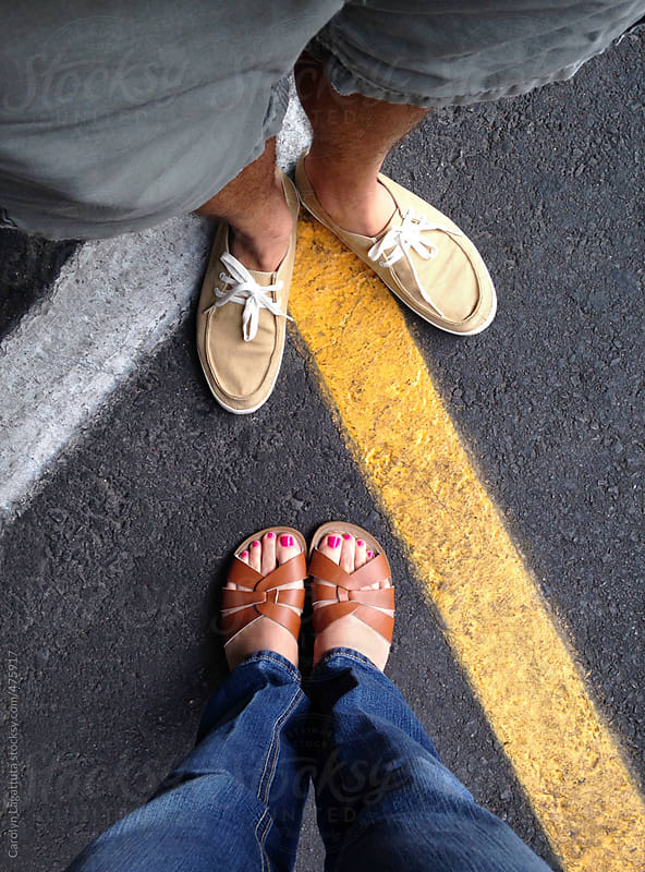 Couple's feet at what seem to be a crossroads by Carolyn Lagattuta for Stocksy United