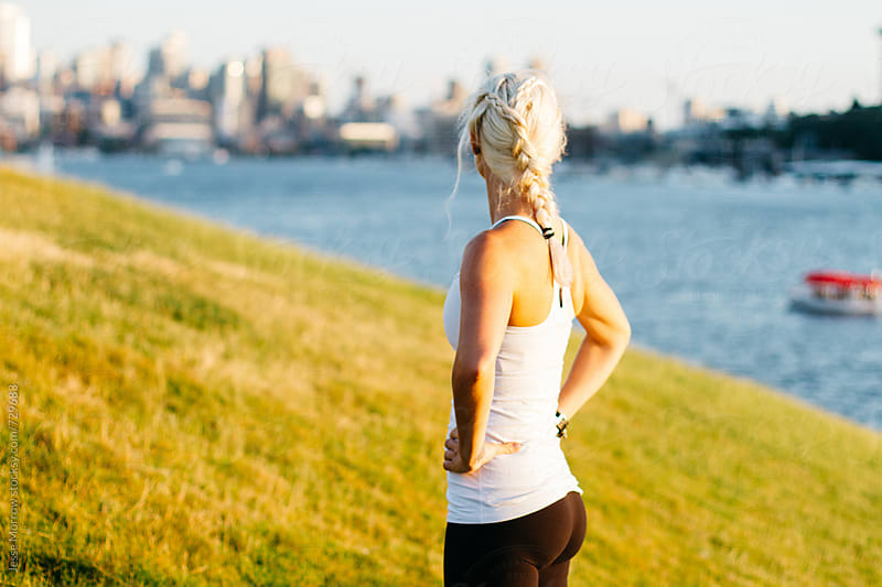 young woman stretching and warming up before workout in city by water by Jesse Morrow for Stocksy United