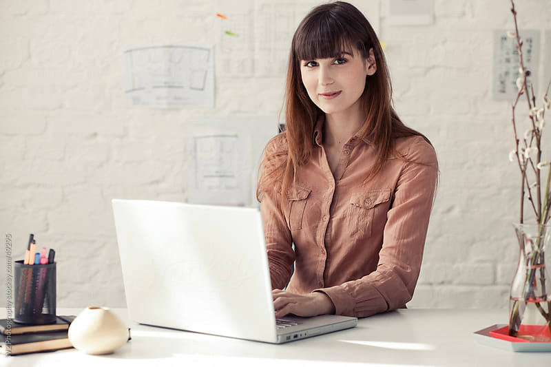 Fashionable woman working on a laptop in a studio. by W2 Photography for Stocksy United