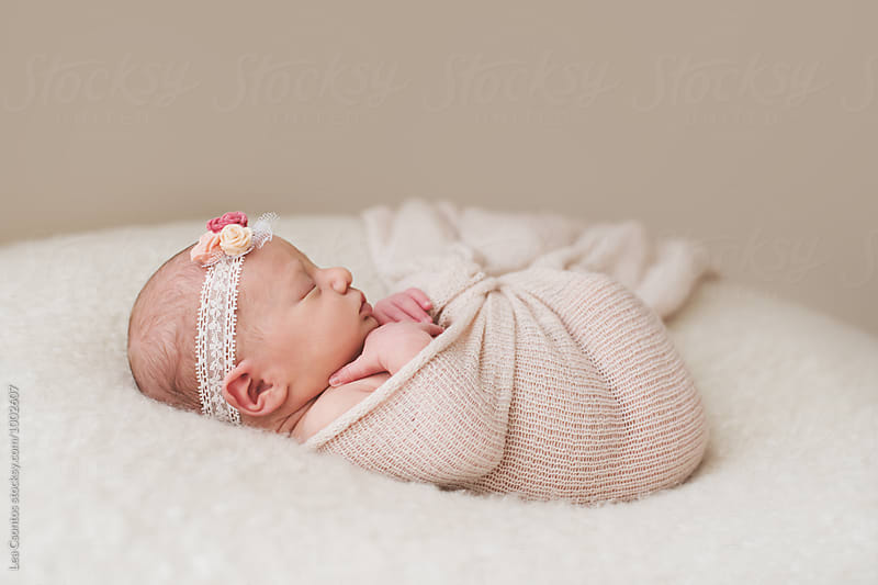 Newborn baby wrapped up and sleeping by Lea Csontos for Stocksy United