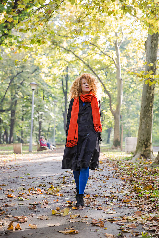 Woman walking in a park on an autumn day by Jovo Jovanovic for Stocksy United