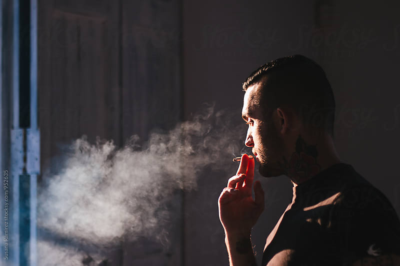 Portrait of man smoking by Susana Ramírez for Stocksy United