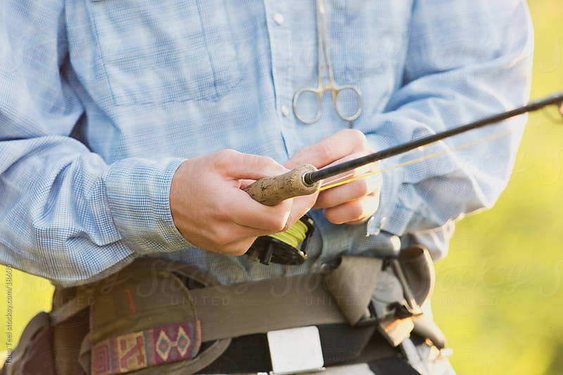 A fly fisherman holding the rod and reel. by Tana Teel for Stocksy United