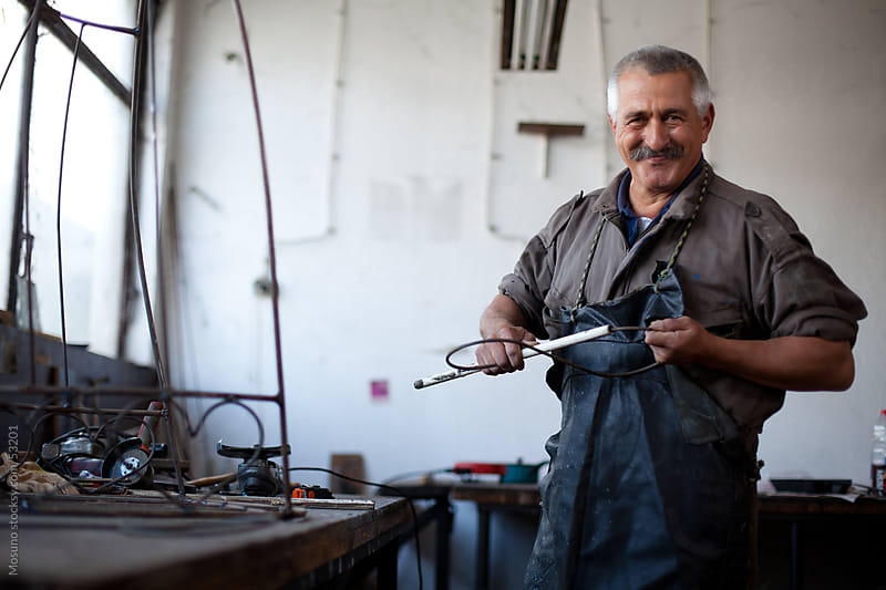 Old craftsman in his workshop. by Mosuno for Stocksy United