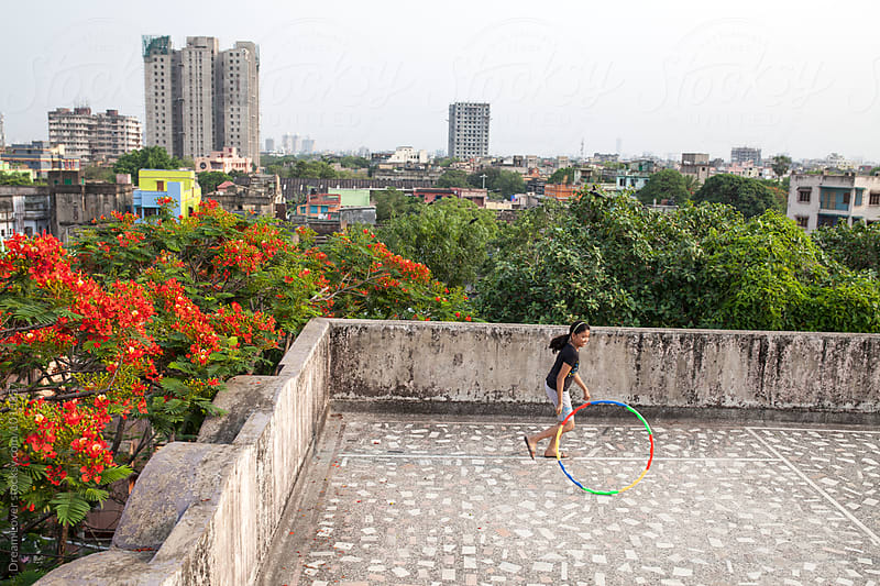 Teenage girl playing with Hula Hoop in roof top by PARTHA PAL for Stocksy United