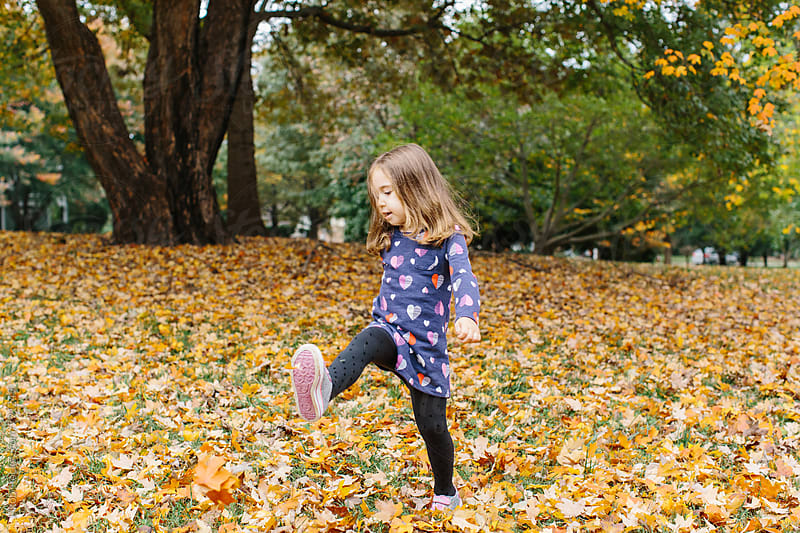 Cute young girl kicking leaves in a park by Jakob for Stocksy United