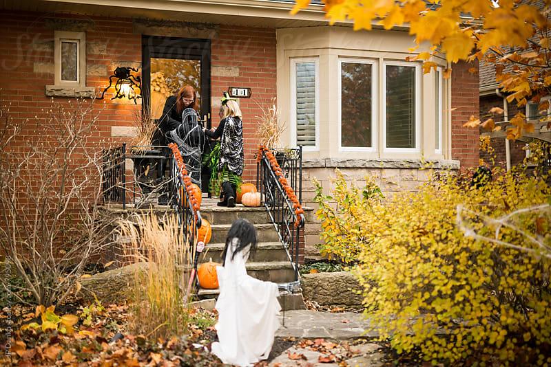 Boy and Girl in Halloween Costume Trick or Treat on Halloween in Neighborhood by JP Danko for Stocksy United