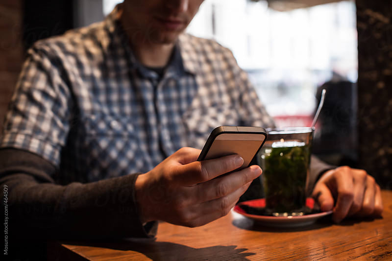 Man Using His Smartphone in a Cafe by Mosuno for Stocksy United