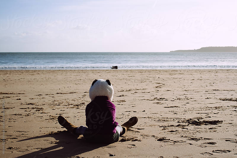 A little girl in a panda hat sitting on a beach looking at the sea. by Helen Rushbrook for Stocksy United