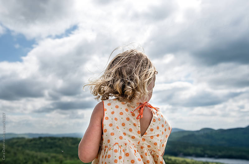 Young girl looks over over a mountain landscape on a cloudy day by Cara Dolan for Stocksy United