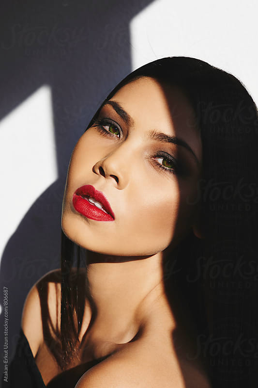 Sunny Portrait of a female model with red lips by Atakan-Erkut Uzun for Stocksy United