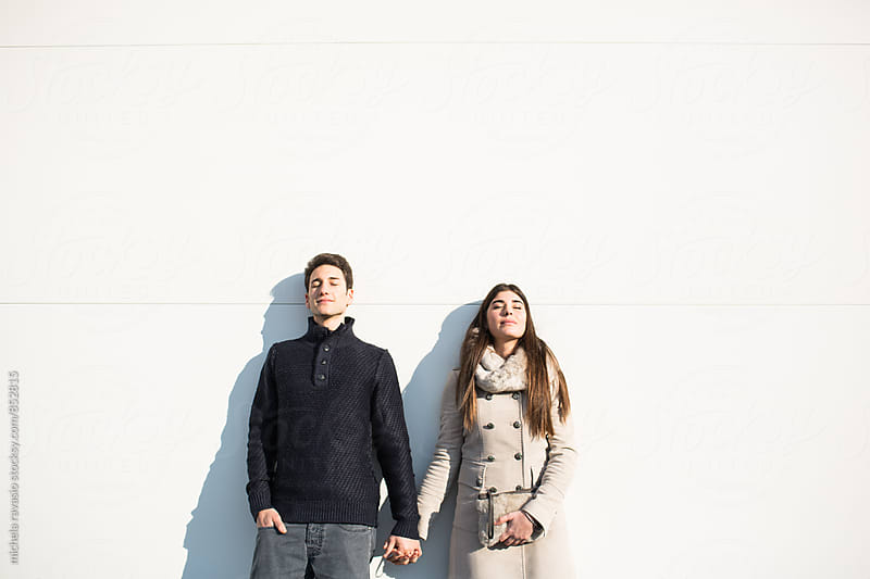Young couple enjoying the sun leaning against a white wall by michela ravasio for Stocksy United