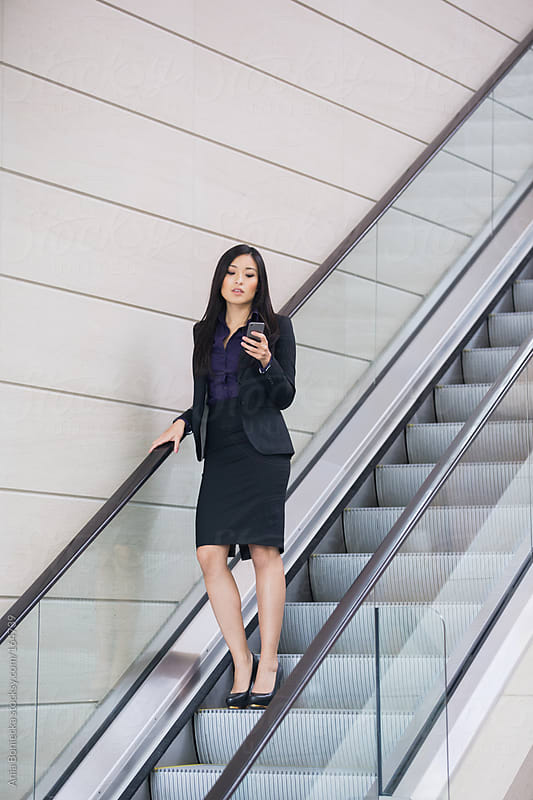 An asian businesswoman standing on an escalator checking her phone for messages by Ania Boniecka for Stocksy United