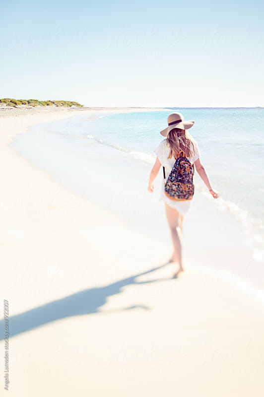 Teenage girl with hat and backpack walks along the white sand of Turquoise Bay after a day at the beach by Angela Lumsden for Stocksy United