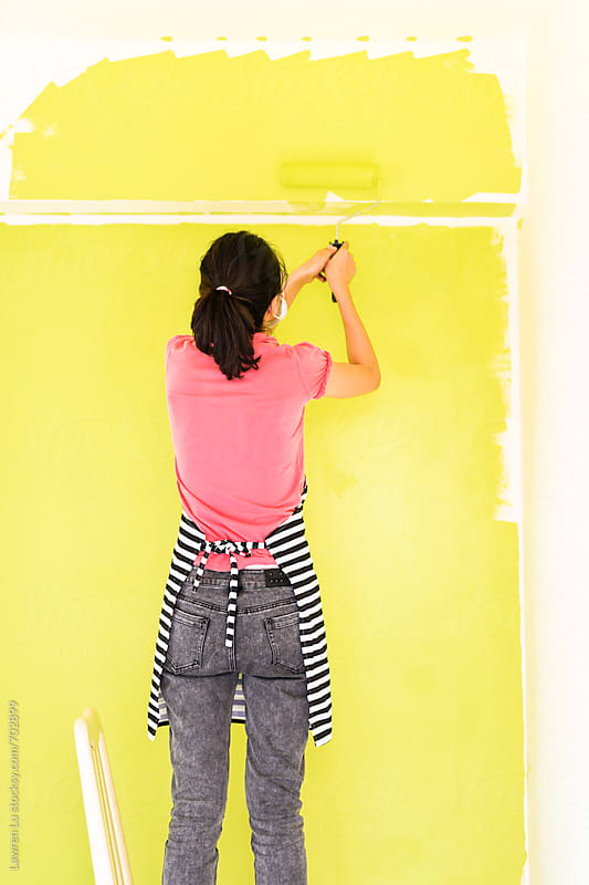 Woman painting her home by rollers by Lawren Lu for Stocksy United
