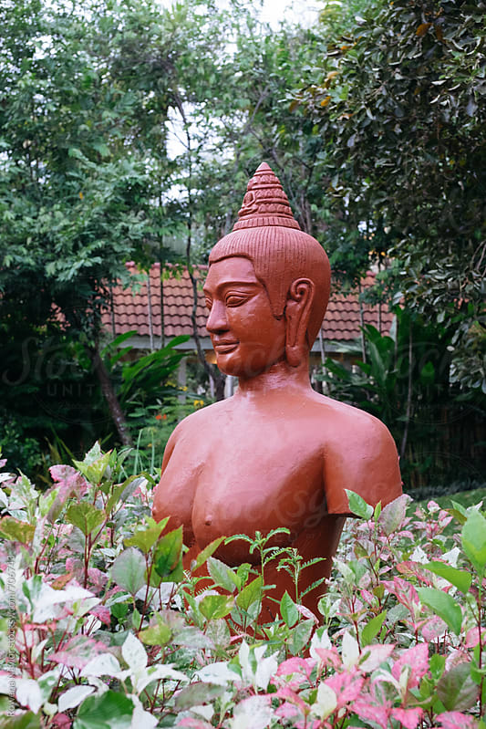 Buddha statue amongst tropical garden by Rowena Naylor for Stocksy United