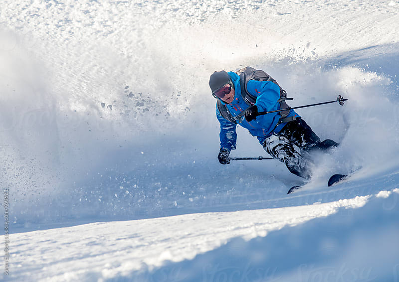 Man skiing  deep powder slope in the mountains by Soren Egeberg for Stocksy United