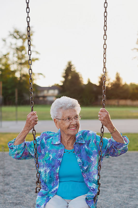 Happy caucasian senior woman smiling outside - sitting on swings by Rob and Julia Campbell for Stocksy United