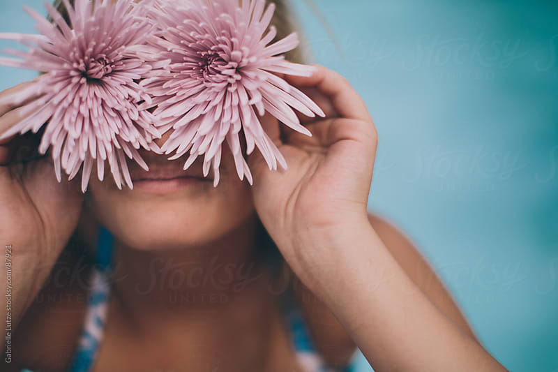 Girl with flowers up to her eyes by Gabrielle Lutze for Stocksy United