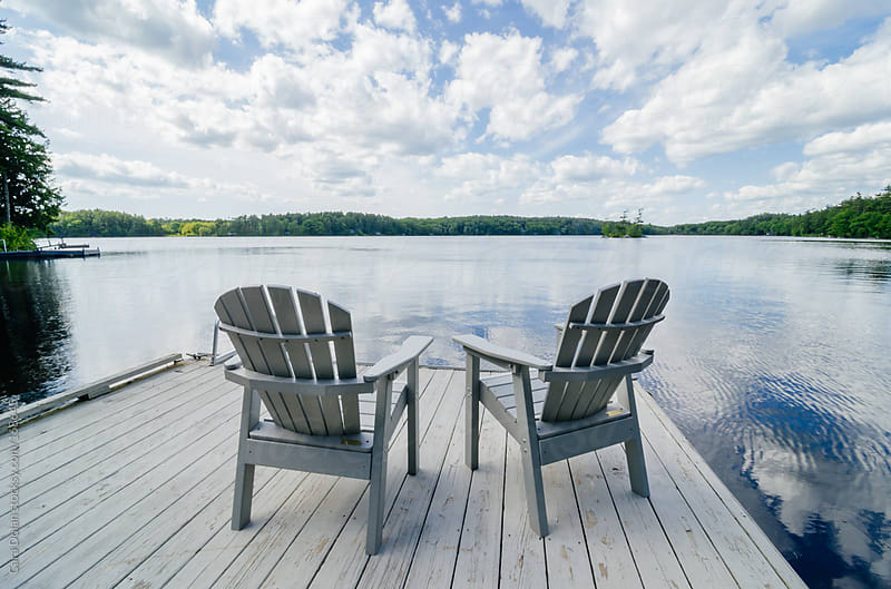 Two chairs sit on a dock overlooking a lake by Cara Dolan for Stocksy United