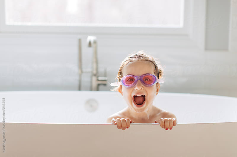 Cute and excited toddler peeking out from a big bathtub by Jakob for Stocksy United