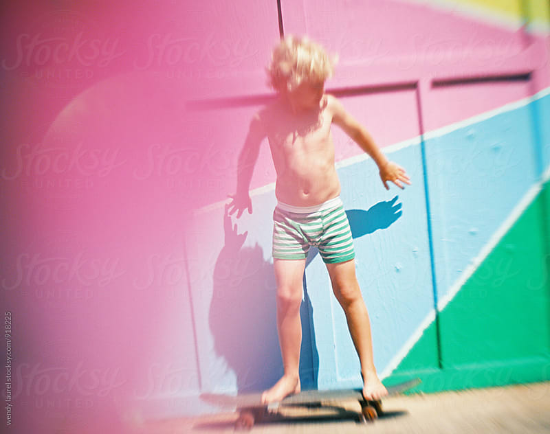 little boy in striped shorts on skateboard in front of colored wall with pink by wendy laurel for Stocksy United