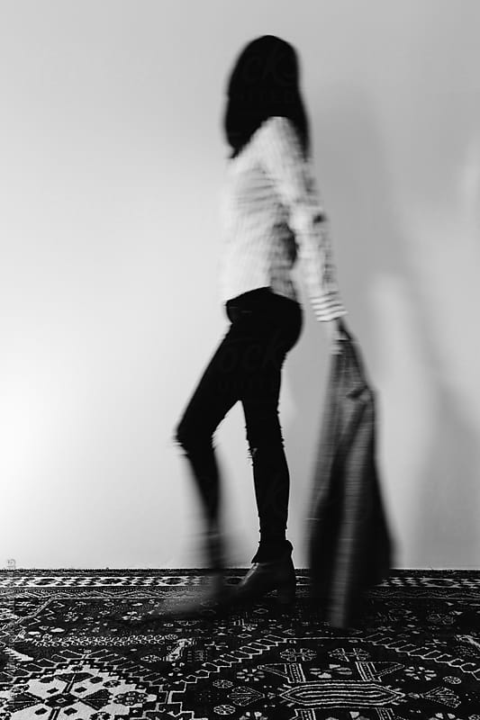 Movement shot of unrecognisable woman walking holding jacket by Jacqui Miller for Stocksy United