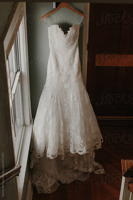 Wedding Dress Hanging by Window by Sidney Morgan for Stocksy United