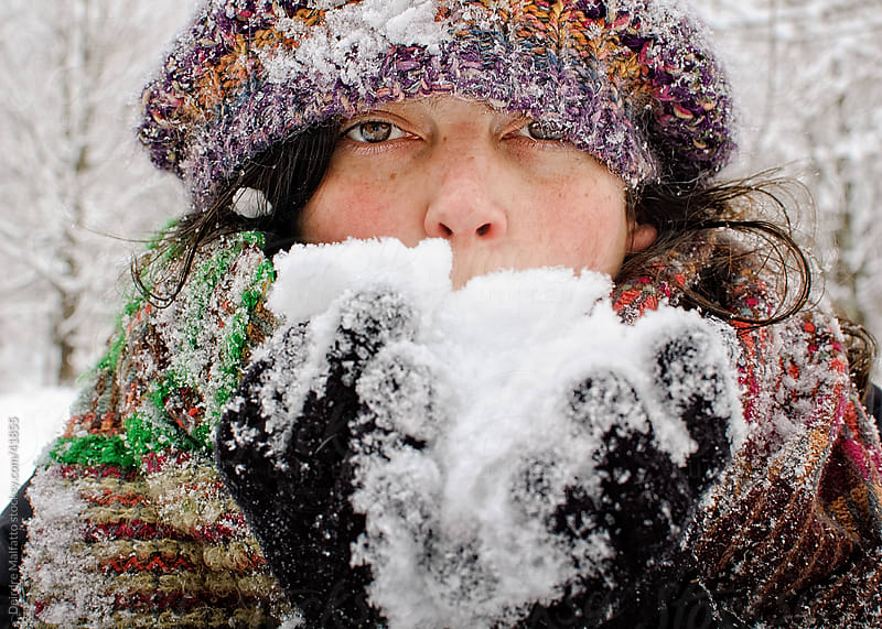 Woman in hat and scarf holding snow  by Deirdre Malfatto for Stocksy United