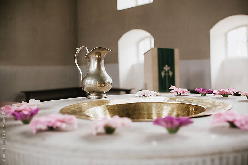Flowers arranged around a Baptismal Font with Baptismal Pitcher by Claudia Lommel for Stocksy United