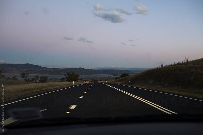 Driving on the highway at dusk by Reece McMillan for Stocksy United