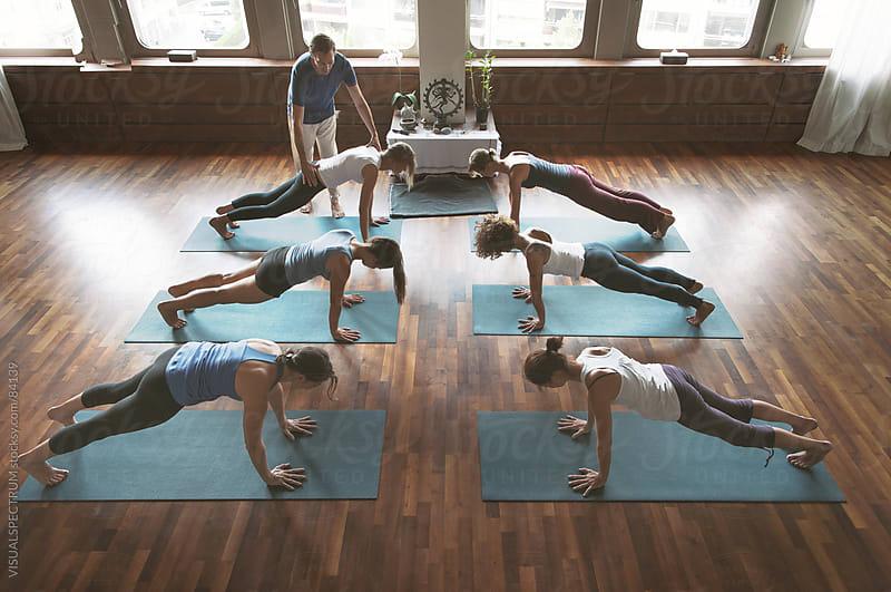 Yoga Teacher Assisting Student by Julien L. Balmer for Stocksy United