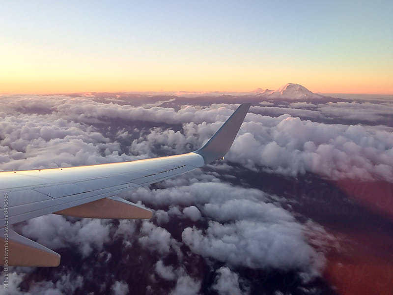Horizontal view of Mount Rainier and clouds at sunrise from the airplane by Mihael Blikshteyn for Stocksy United
