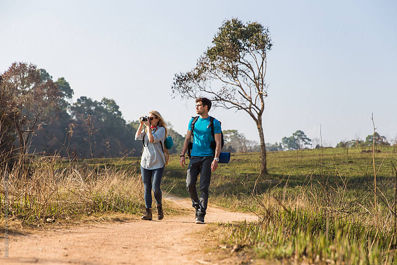 Couple walking with backpacks outdoors - adventure, travel, tourism by Jovo Jovanovic for Stocksy United