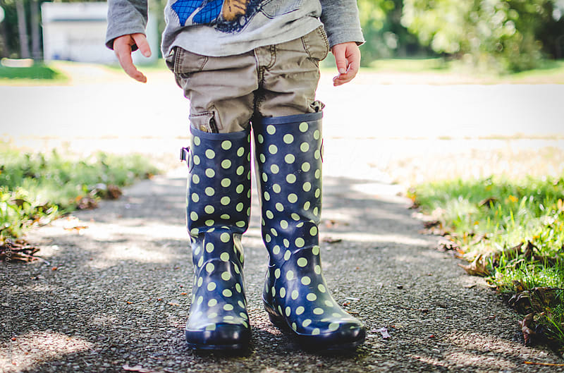 Child standing in adult rain boots by Lindsay Crandall for Stocksy United