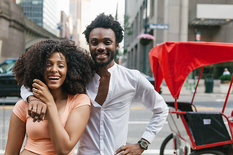 Afro American Couple Smiling in the Street by VICTOR TORRES for Stocksy United