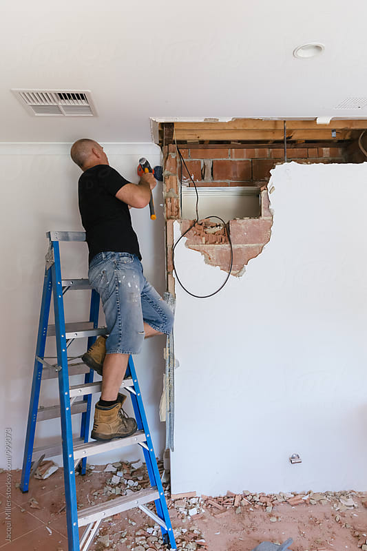 Home Renovator demolishing an internal brick wall by Jacqui Miller for Stocksy United