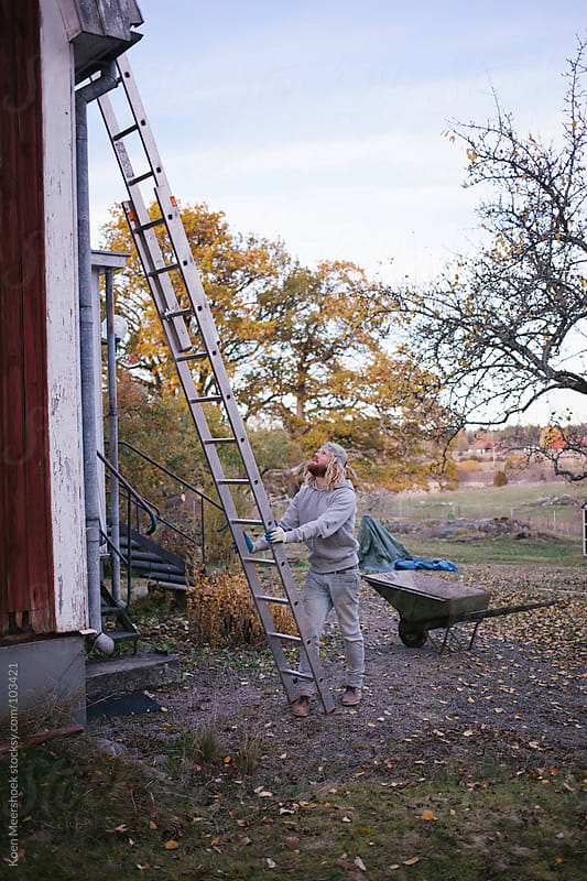 A man holding a ladder to climb the roof. by Koen Meershoek for Stocksy United