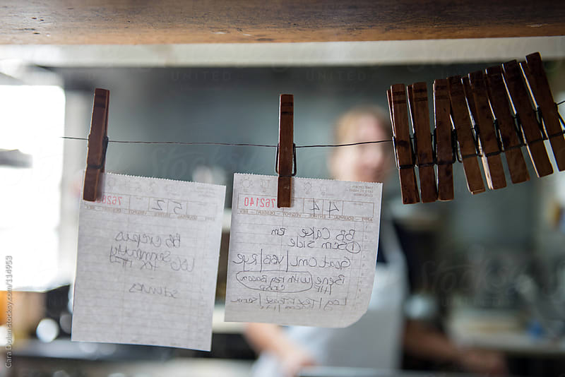 Order tickets in a restaurant held onto a string with clothespins by Cara Dolan for Stocksy United