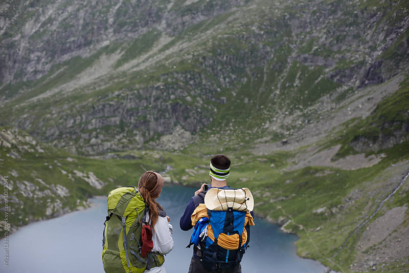 Young couple of backpackers enjoying a lake view of the Pyrenees by Miquel Llonch for Stocksy United