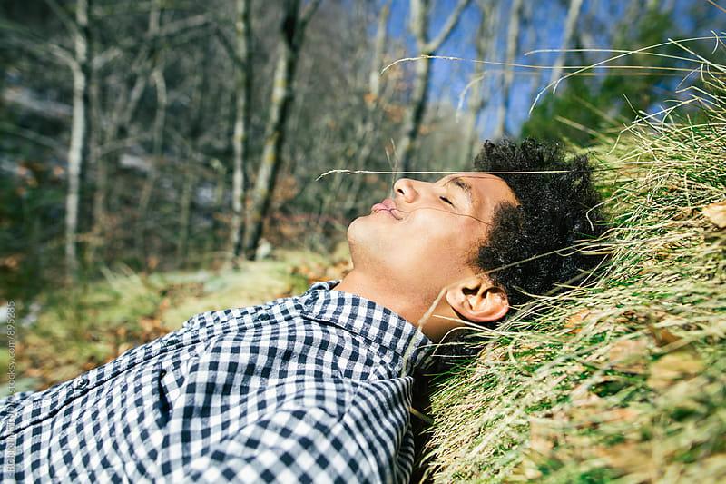 Man enjoying a sunny day lying on grass. by BONNINSTUDIO for Stocksy United