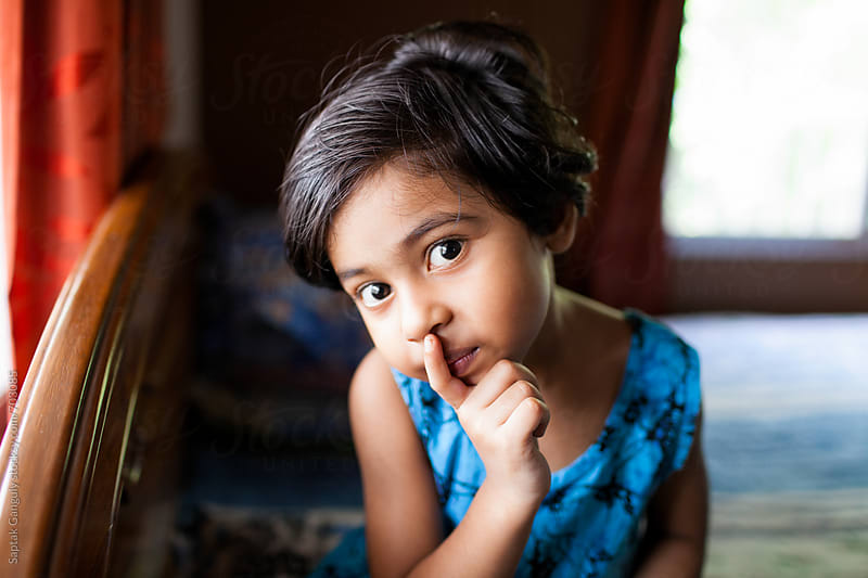 Cute little girl with finger on her lips by Saptak Ganguly for Stocksy United