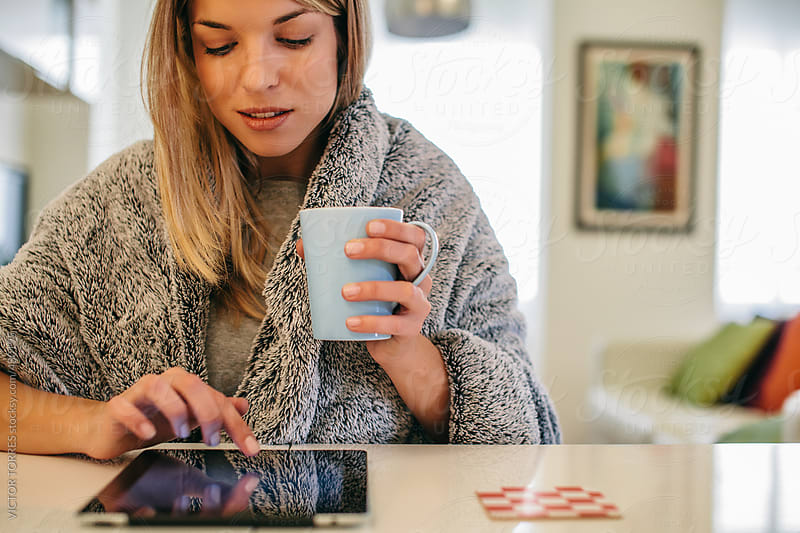 Woman with a Grey Blanket using a Digital Tablet at Home by VICTOR TORRES for Stocksy United