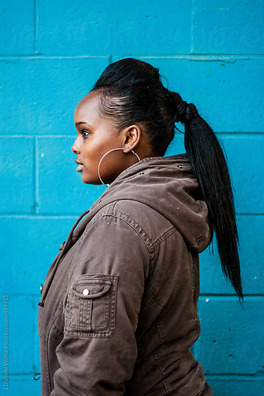 African American woman with a profile view against blue wall by J Danielle Wehunt for Stocksy United