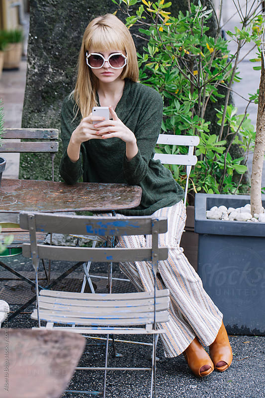 Stylish Woman Texting at Cafe by Alberto Bogo for Stocksy United