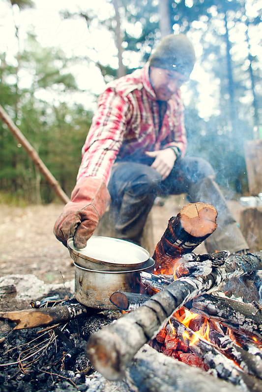 Young man cooking on a campfire by Denni Van Huis for Stocksy United