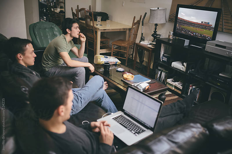 Group of Young Male University Students - Roommates Watching TV and Laptop on Couch by Joselito Briones for Stocksy United